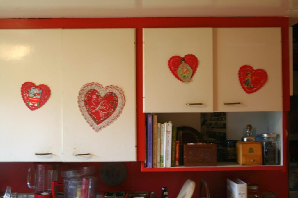 i decorated the cupboards by taking some vintage valentines i found at an antique store and gluing them onto some paper doilies - Vintage Valentine Decorations